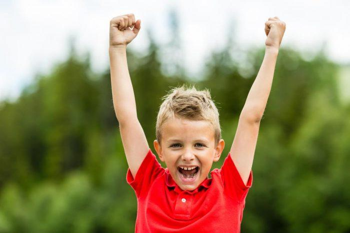 Довольный мальчик тянет руки вверх