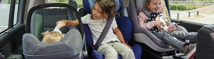 Дети в автокреслах и в автолюльке на заднем сидении машины