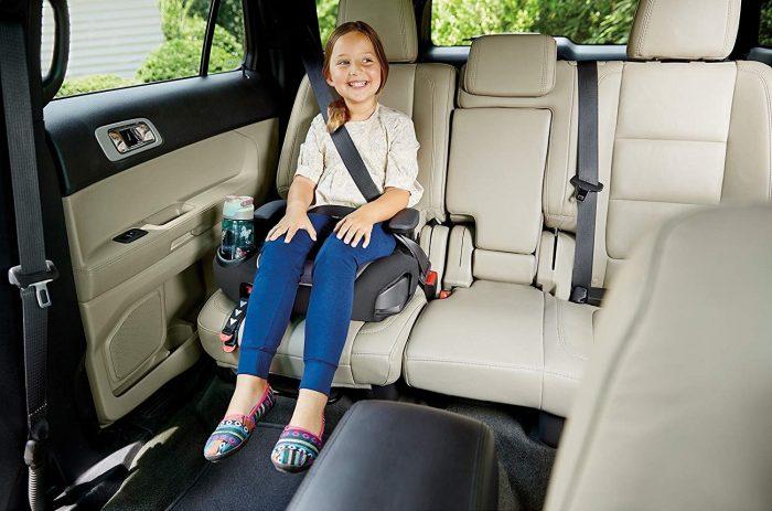 Девочка на бустере на заднем сидении автомобиля