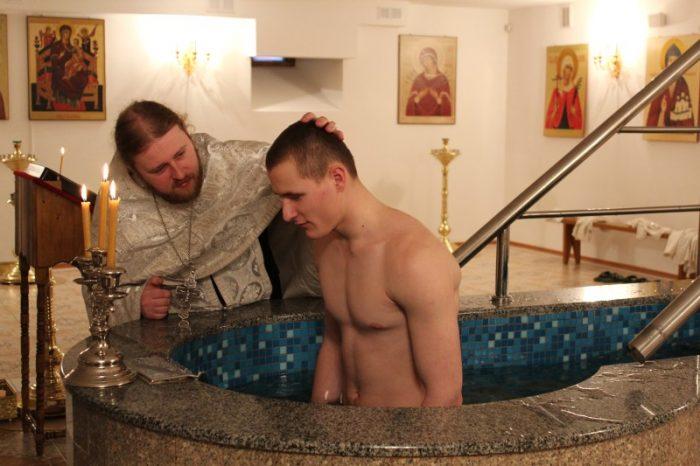 Батюшка крестит взрослого мужчину