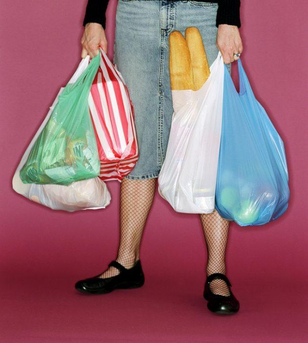 Женщина, обвешанная пакетами с продуктами