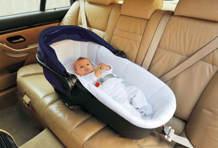 Младенец в автолюльке-кроватке на заднем сидении автомобиля