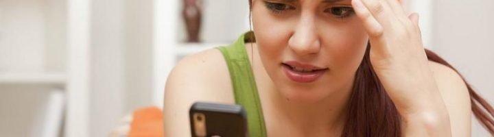 Девушка задумчиво смотрит на мобильный телефон
