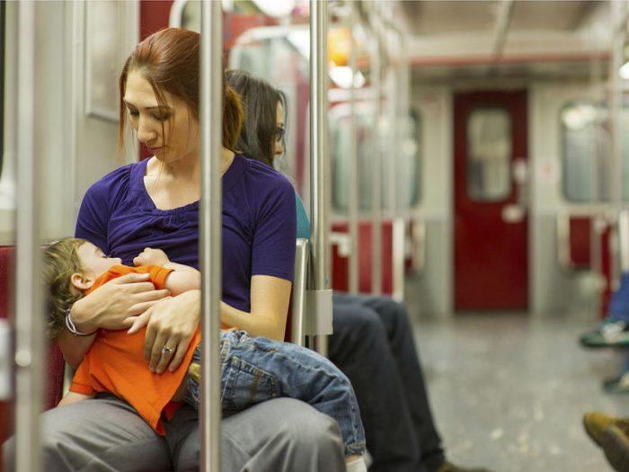 Женщина со спящим мальчиком на руках сидит в общественном транспорте