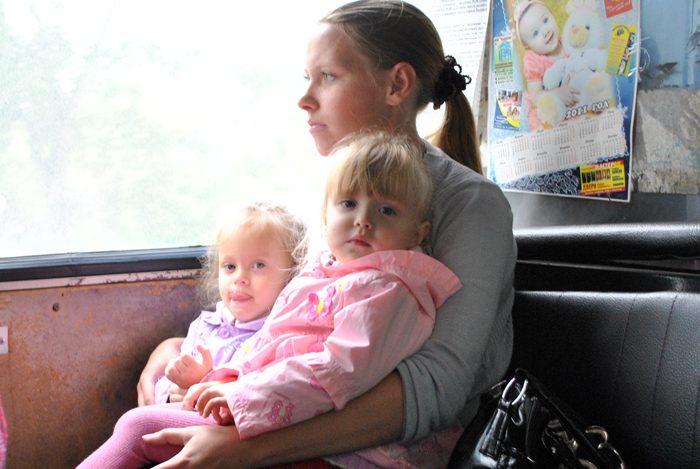 Мама с двумя маленькими дочками на коленях
