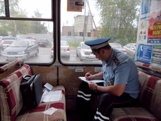 Сотрудник полиции что-то записывает, сидя в салоне автобуса