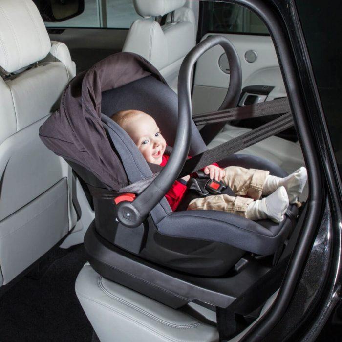 Младенец в автолюльке-кресле на заднем сидении автомобиля