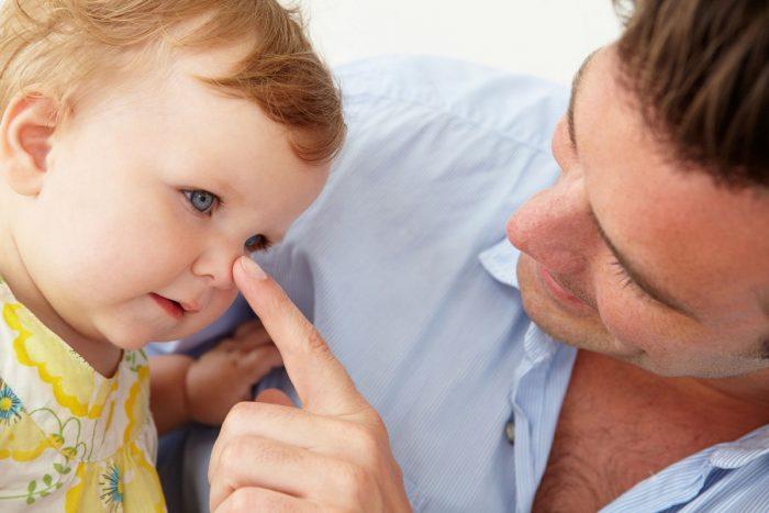Отец трогает носик сына