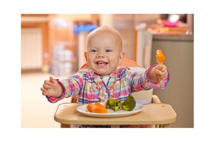 Малыш сидит в детском стульчике перед тарелкой с овощами