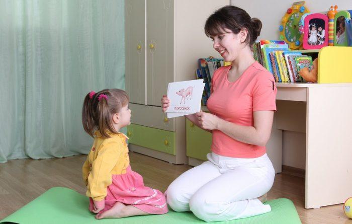 Мама показывает дочке карточки с изображением животных
