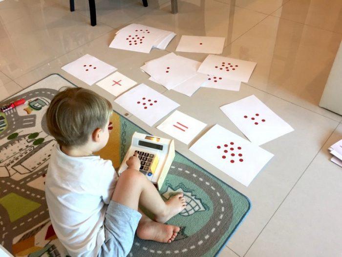 Мальчик сидит на полу, возле него карточки Домана для обучения счёту