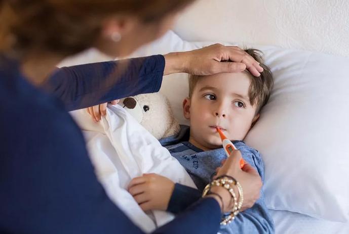Мальчик в постели, мама меряет ему температуру во рту