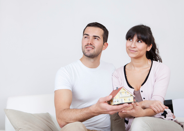 Муж и жена держат в руках макет дома и о чём-то думают