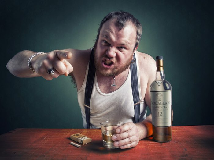Пьяный мужчина за столом с бутылкой и стаканом что-то доказывает
