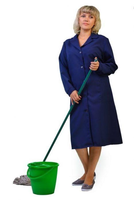 Женщина в синем халате для уборки держит в руке швабру, рядом стоит ведро