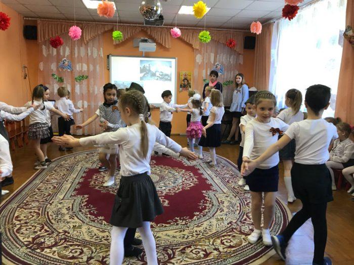 Дети танцуют парами на утреннике