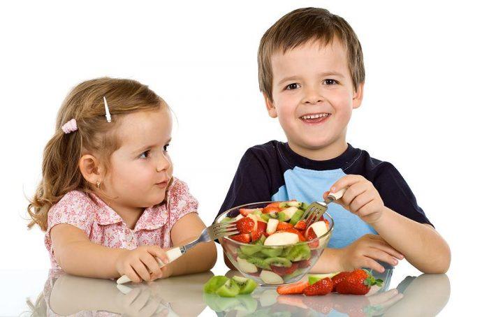 Мальчик и девочка едят фруктовый салат