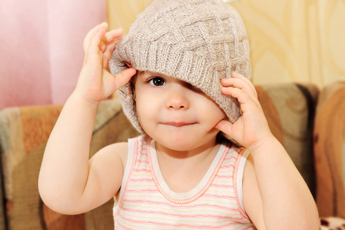 Ребёнок надевает сам себе шапку