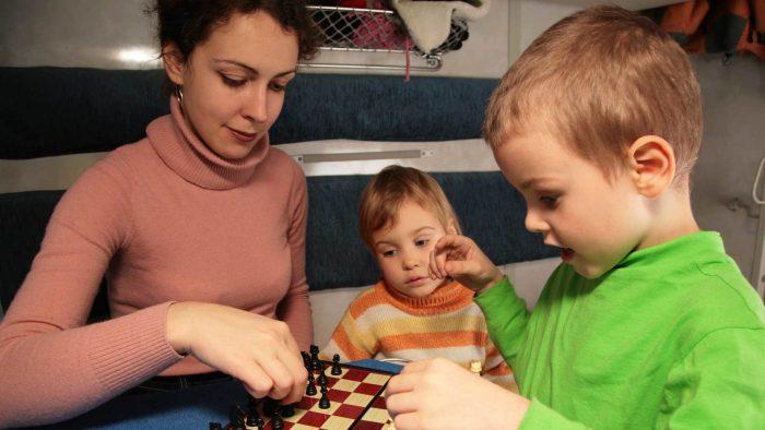 Мама играет в шахматы с мальчиком, второй ребёнок смотрит