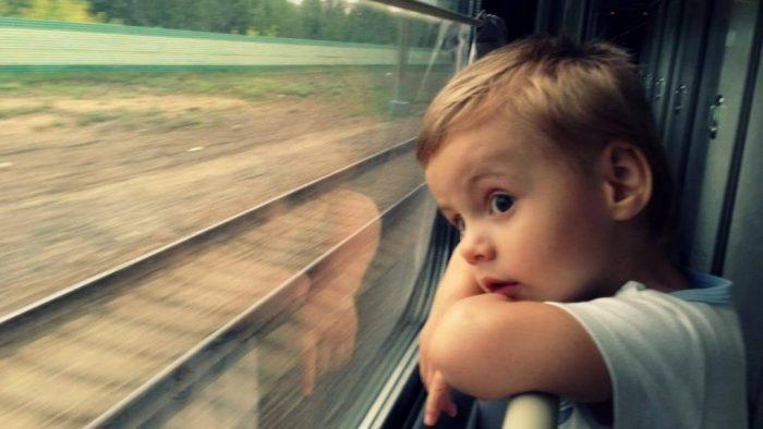 Мальчик смотрит в окно поезда