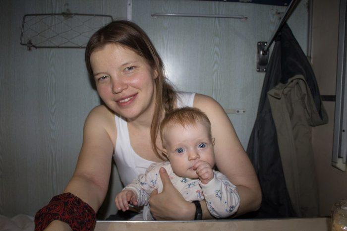 Мама сидит с малышом на руках в купе