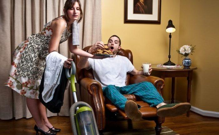 Муж лежит в кресле, жена с пылесосом в руках угощает его печеньем