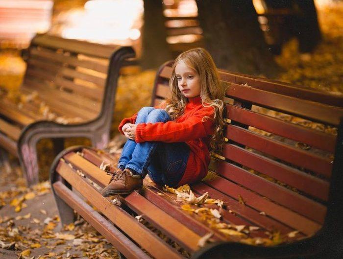 Девочка с задумчивым видом сидит на лавочке