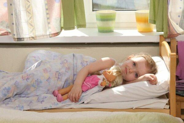 Девочка лежит в кровати, прижав к себе куклу