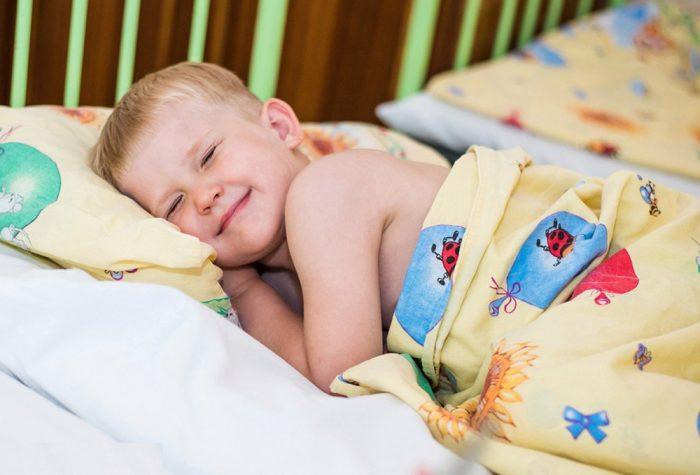 Мальчик лежит на кровати, зажмурив глаза