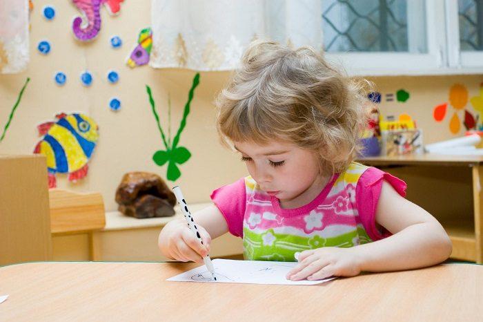 Девочка рисует в детском саду