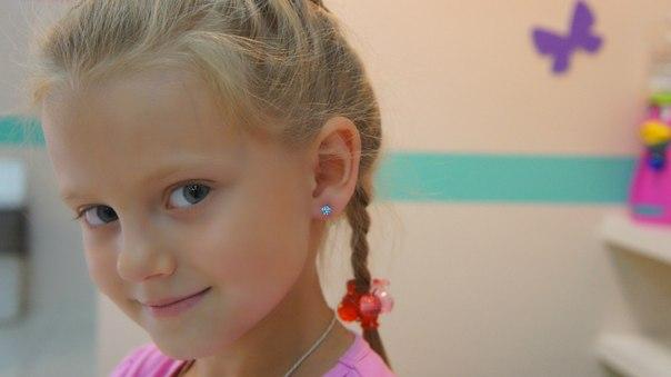 Девочка с серёжками и волосами, собранными в косички