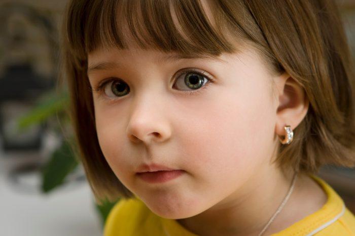 Девочка примерно 3–4 лет с серьгами в ушах