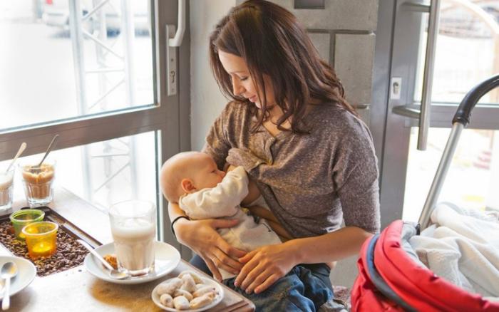 Мать кормит грудью младенца прямо в кафе