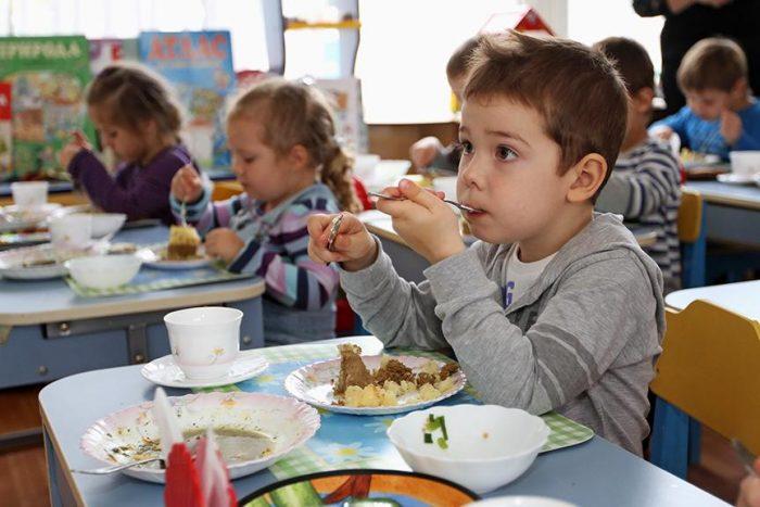Дети в детском саду едят мясную запеканку