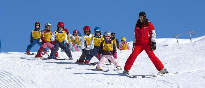 Дети на лыжах идут за инструктором