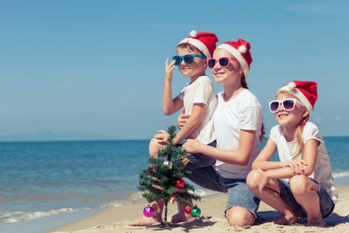 Трое детей в шапочках Санта Клауса сидят на побережье