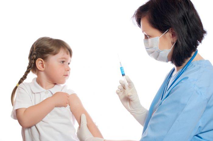 Женщина в медицинской форме ставит прививку от гриппа девочке