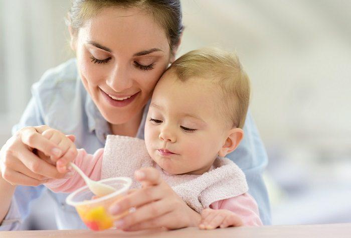 Мама кормит ребёнка с ложечки