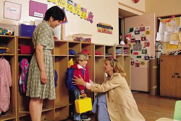 Мама, ребёнок и воспитатель в раздевалке