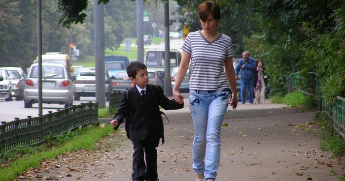 Мама ведёт сына со школьным портфелем на плечах за ручку