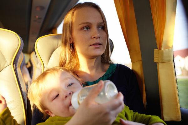 Мама с ребёнком на руках едет в транспорте