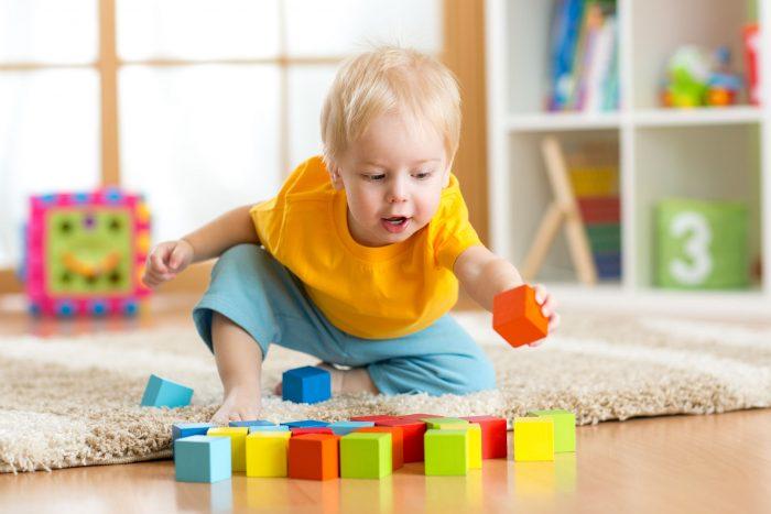 Малыш в жёлтой футболке и голубых шортах играет с кубиками