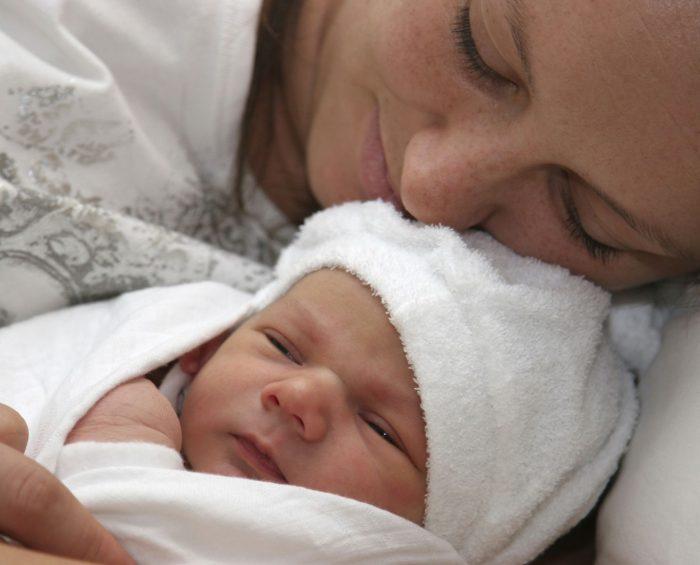 Малыш в бёлой шапочке лежит с мамой