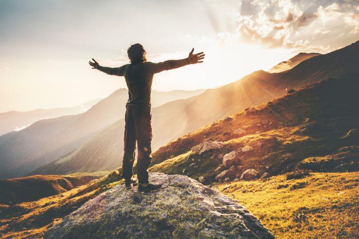 Мужчина стоит на вершине горы, разведя руки в стороны