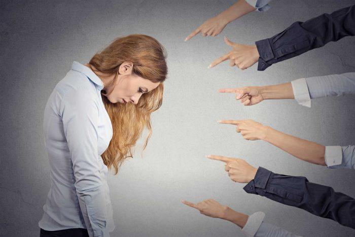 Множество рук указывают на склонившую голову женщину