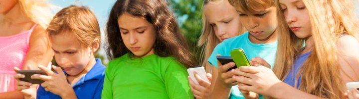 Дети в ярких футболках смотрят в смартфоны