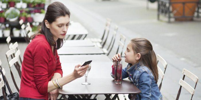 Мама со смартфоном в руках и с дочкой сидят за столиком уличного кафе