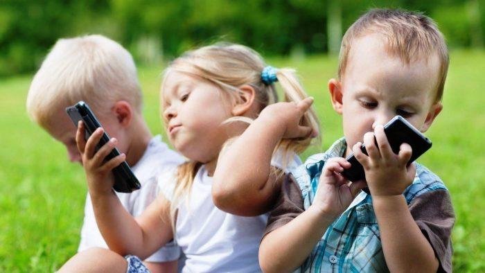 Трое детей на лужайке со смартфонами