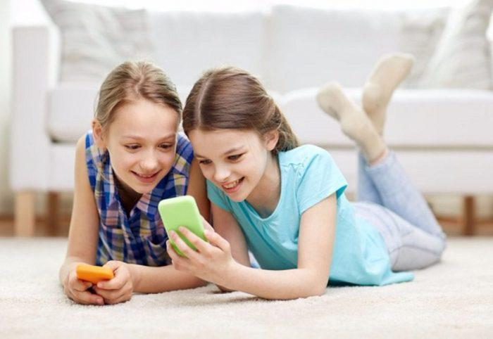 Две девочки лежат на полу со смартфонами и улыбаются