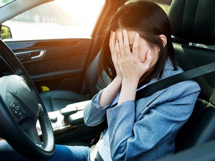 Девушка за рулём закрывает лицо руками